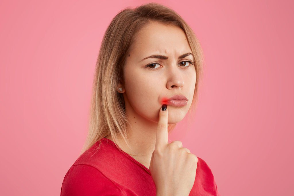 Close up shot of pretty woman being affected by herpes virus, keeps fore finger near lips, has dissatisfied facial expression, wears red clothing poses over pink background. People and illness concept